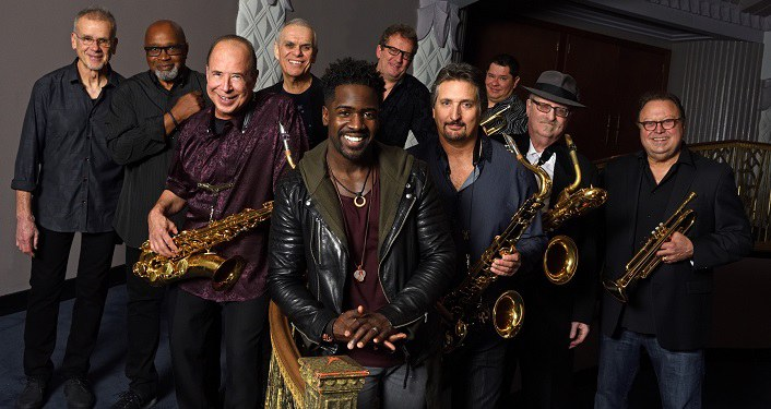 Tower of Power Press Photo; 10 men standing, grouped together; 3 holding saxaphones, 2 holding trumpets. All wearing darker clothing, smiling at the camera