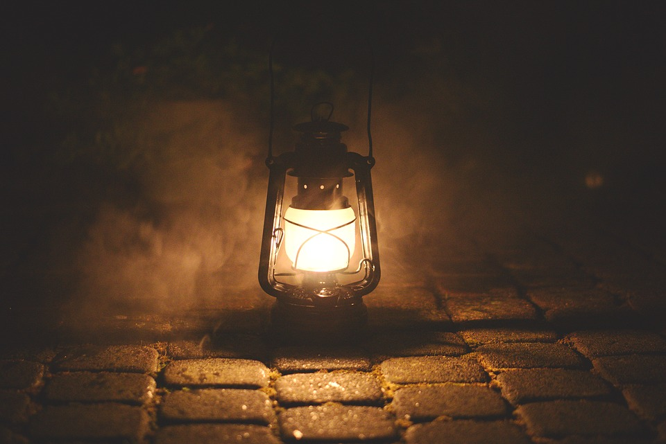 A lantern on a dark, foggy, cobblestone street.