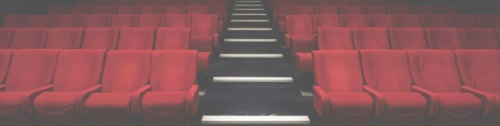 Four rows of theater seats with a staircase dividing them.