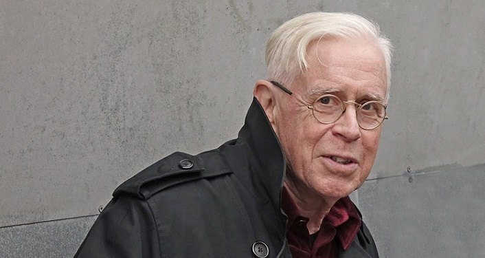 image of older man with white hair, wearing glasses, black jacket over red-plaid shirt, Bruce Cockburn