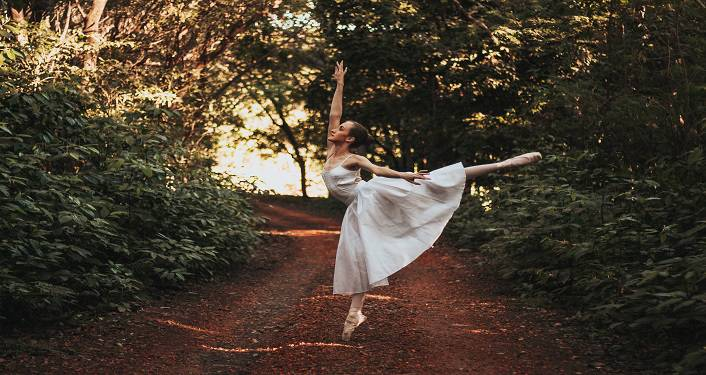 image of ballet dancer dressed in white, dancing on a dirt road in the woods. Symphonic Dances