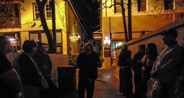 image at night with group of people gathered round tour guide on GhoSt Augustine Paranormal Tours