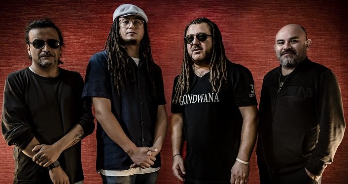 press photo of Chilean reggae veterans Gondwana; four men, standing; all wearing black shirts and slacks; two with long hair, two short hair