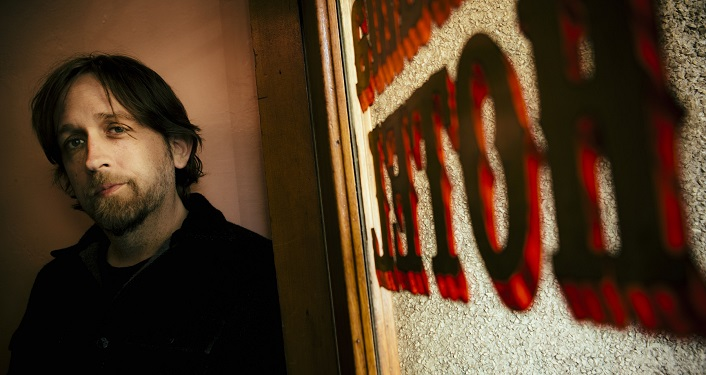press photo of acclaimed singer/songwriter Hayes Carll. tinted photo with man with dark shoulder length hair wearing black button shirt.