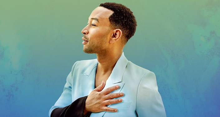 press photo of John Legend; looking to his right, wearing light turqiouse colored jacket, standing with right hand over his heart.