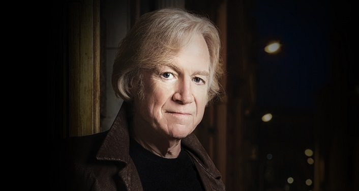 press photo English singer-songwriter Justin Hayward; man with light sandy colored hair, wearing dark shirt, brown jacket