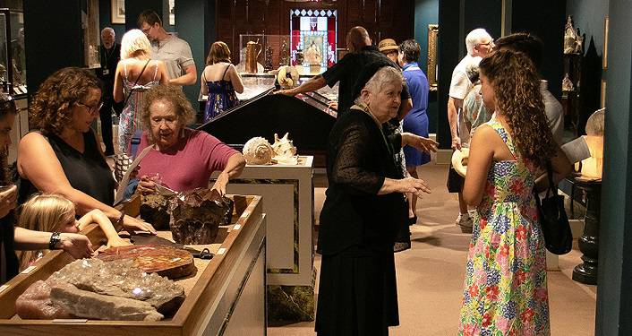people in the Science Room at Lightner Museum; men and women of various ages looking at exhibits.