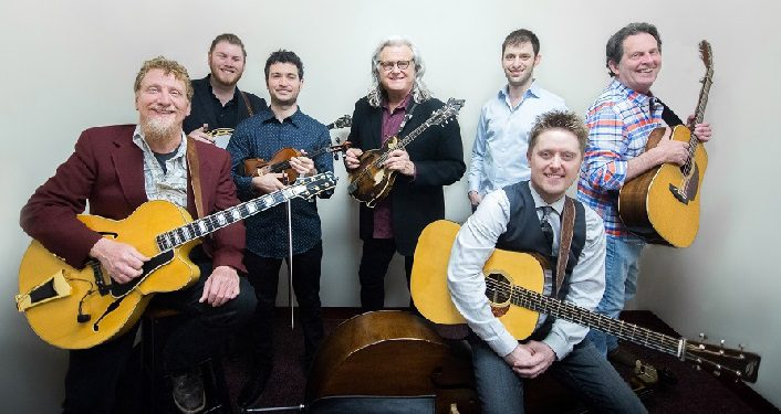 press photo of Ricky Skaggs & Kentucky Thunder Press Photo; 7 men, three holding guitars, one holding a mandolin, one holding fiddle, one a banjo