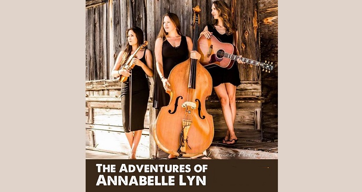 image of 3 women; all wearing black sleevless dresses, all with long hair. One holding fiddle, one holding cello, one holding guitar. Text: The Adventures of Annabelle Lyn