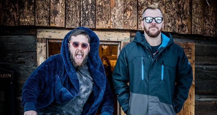 press photo of Electronic-funk duo The Floozies; 2 men approx in late 20s, early 30s. both wearing sunglasses, hoodies; standing with hands in pockets.