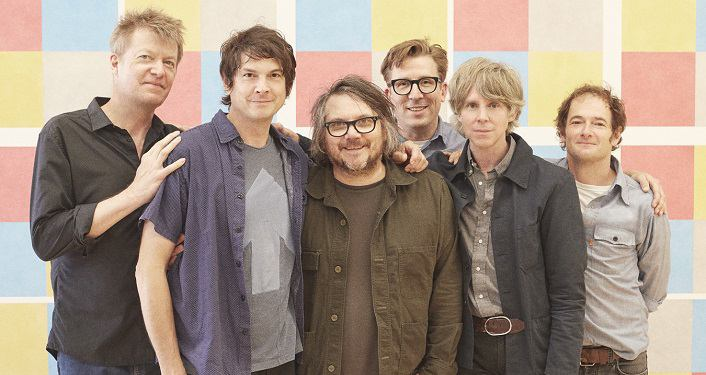 image of Wilco, 6 guys wearing casual clothes, smiling into camera