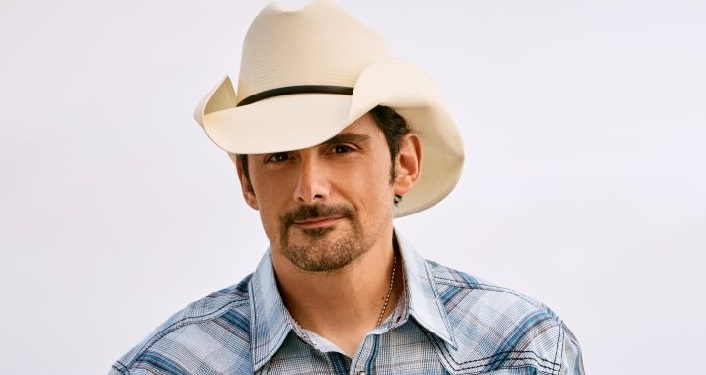 press photo of Country music superstar Brad Paisley; man with short, dark hair and mustache wearing light colored cowboy hat, blue plaid shirt