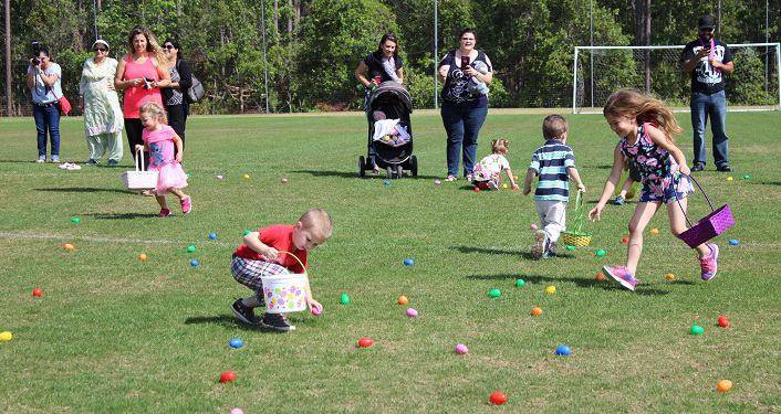 Kids filling their baskets with Easter Eggs lying on the grass, parents standing nearby watching; St. Johns County Parks & Rec Annual Easter Egg Hunts
