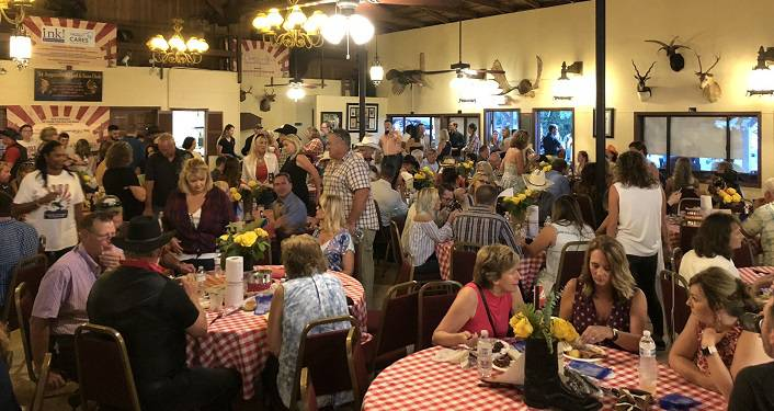 image of people sitting at round, checker-cloth covered tables; some standing in background. INK! 5th Annual Boot Scootin' BBQ