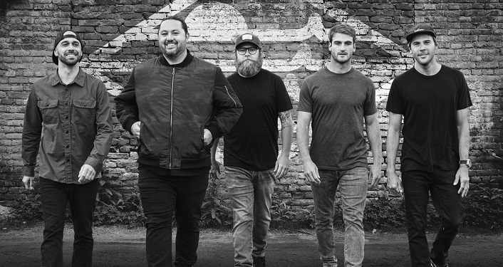 black & white image of 5 men, standing looking at camera, all wearing casual clothes, jeans, etc...Alternative/reggae group Iration