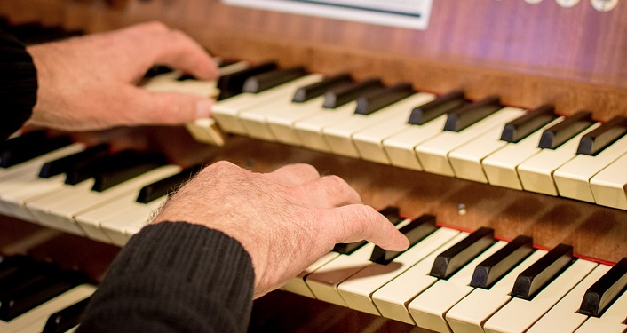 Mans hands playing an organ during Lenten Organ Series