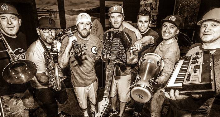 Reggae-rock favorites Slightly Stoopid press photo; black & white image of 7 men standing in semi-circle each one holding a different instrument; bongo drums, guitar, keyboard, trumpet, sax.