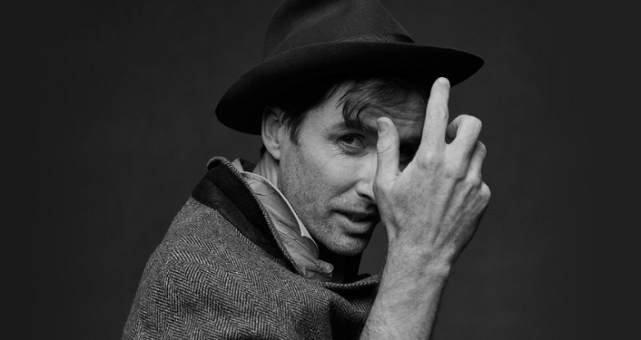 black & white image, Internationally acclaimed musician, songwriter and composer, Andrew Bird. head shot man with dark hair wearing hat, grey jacket with dark lapel.