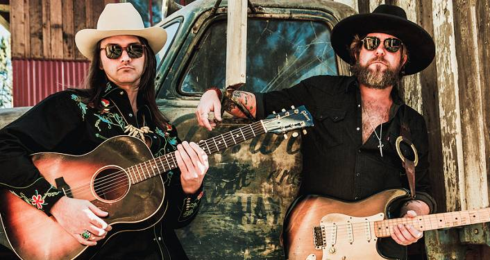The Allman Betts Band; two middle-aged men with long dark hair, each wearing black and holding guitars