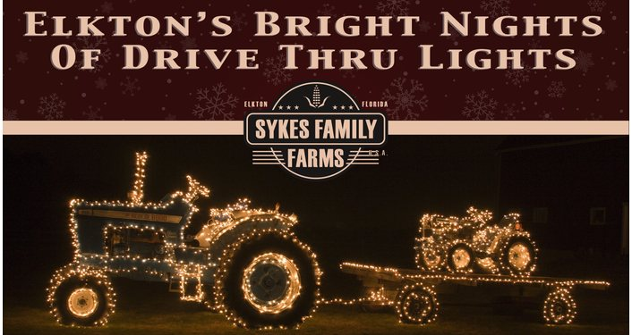 side view of tractor pulling flatbed with small tractor all decorated in white lights; Elkton's Bright Nights of Drive Thru Lights