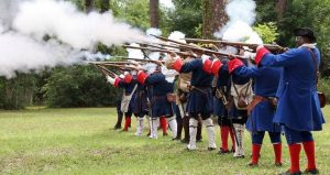 men dressed in 18th century clothing firing muskets during Militia Muster at Fort Mose